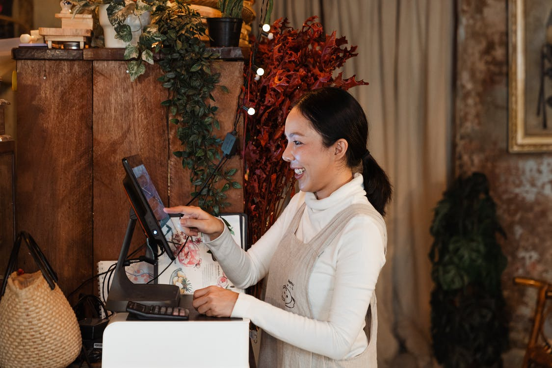Side view of smiling young Asian female cashier wearing apron using modern cash desk with computer screen in cafe with rustic wooden interior