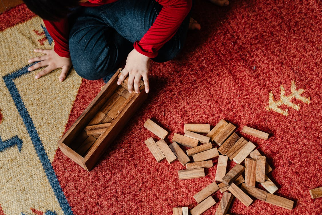 Unrecognizable child playing jenga at home