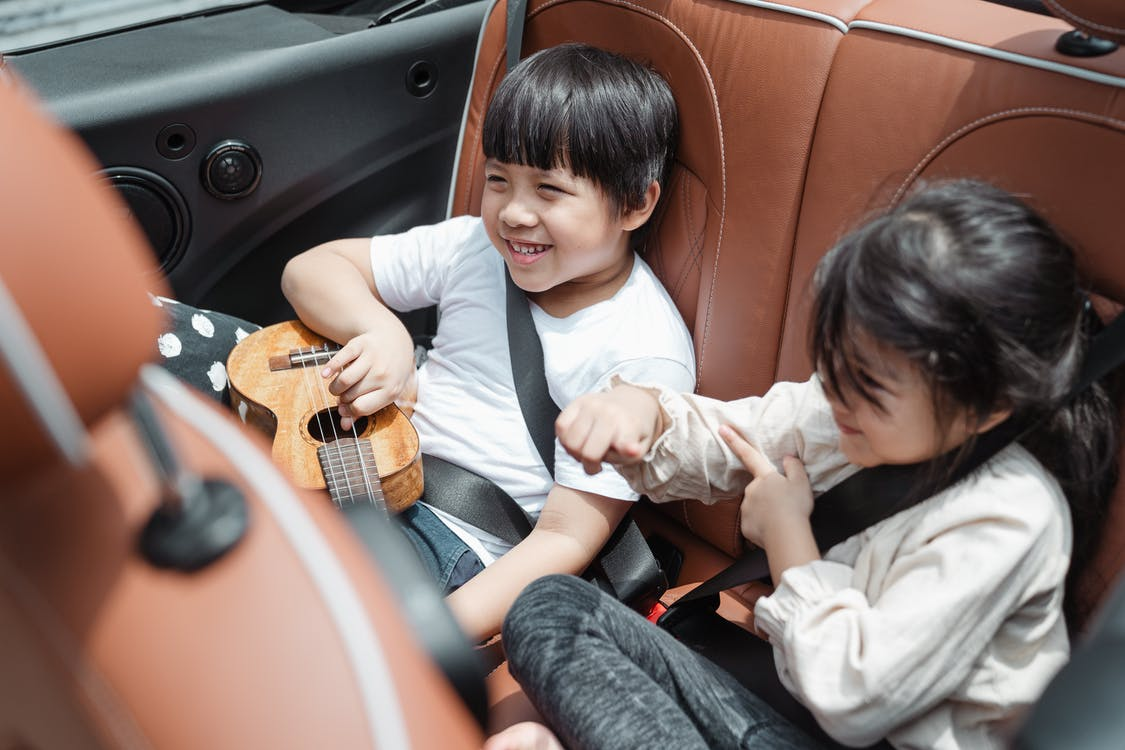 From above smiling ethnic boy and girl in casual outfits sitting fastened in passenger seats with ukulele during road trip together