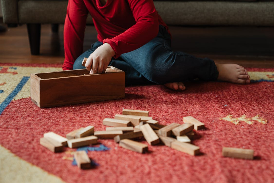 Unrecognizable barefoot kid playing jenga at home
