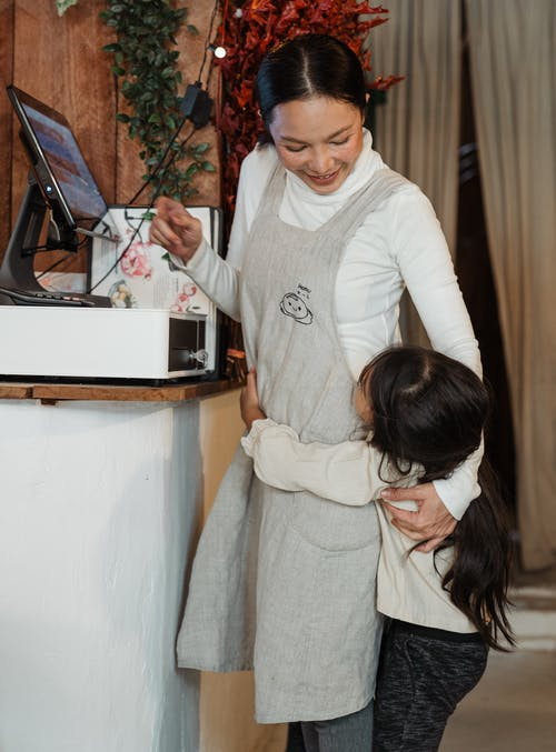 Happy ethnic female waitress embracing cute daughter near cash desk in restaurant