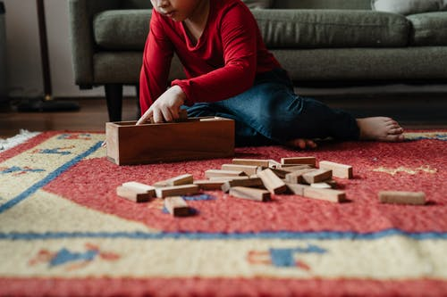 Ground level of cute kid in casual clothes sitting on floor carpet near cozy sofa and playing in jenga tower game with wooden blocks while spending time at home
