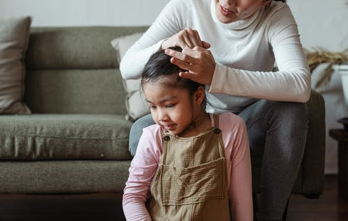 Photo of Woman Tying Her Daughter's Hair