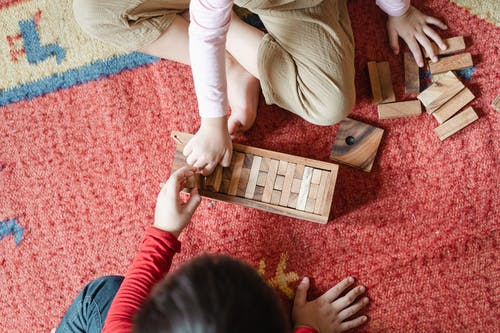 Top view of anonymous barefoot boy and girl in casual clothes sitting on floor carpet and playing with wooden blocks of jenga tower game