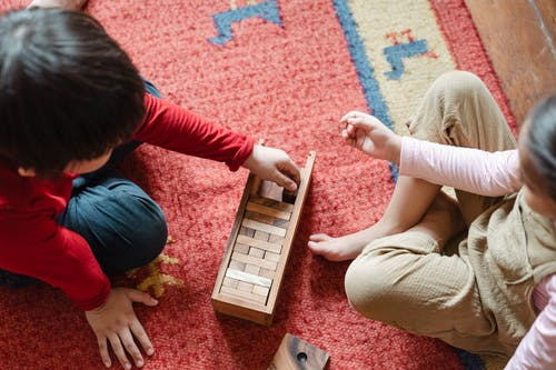 Crop cute kids playing jenga on floor at home