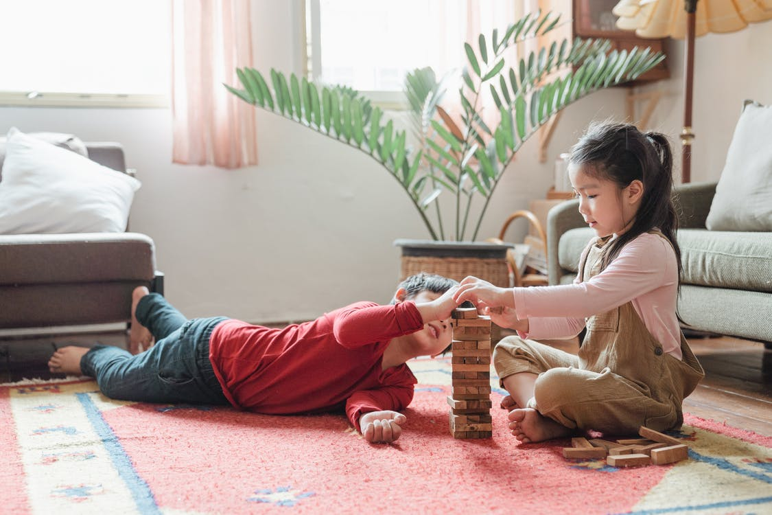 Adorable Asian kids building wooden tower on floor at home