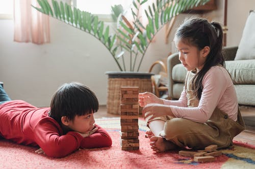 Content Asian children building wooden tower on floor at home