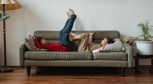 Full body barefoot Asian brother and sister lying on cozy sofa while spending free time in modern living room during weekend