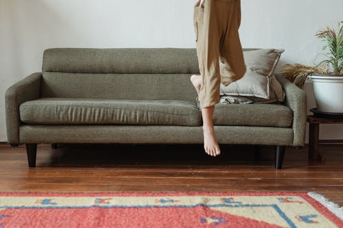 Crop girl jumping from sofa at home