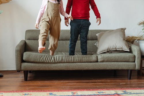 Photo of Two Kids Standing on Gray Sofa