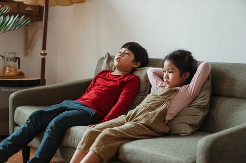 Photo of Two Kids Sitting on Sofa