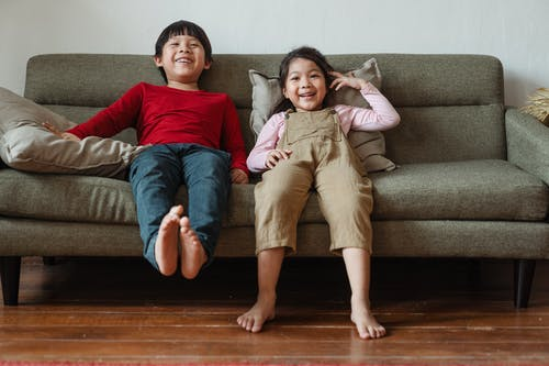 Photo of Two Kids Sitting on Gray Couch