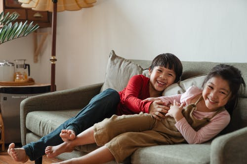 Photo of Two Kids Having Fun While Sitting on Gray Couch