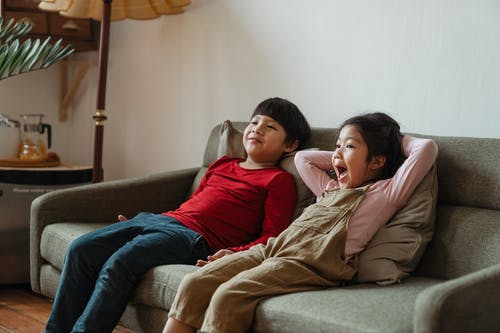 Two Kids Sitting on Gray Couch