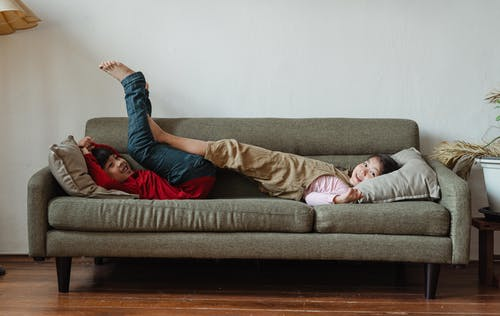 Two Kids Lying Down on Gray Sofa
