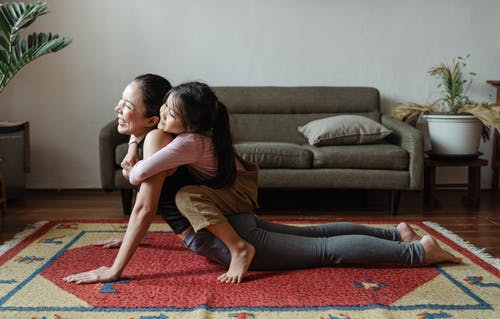 Photo of Girl Hugging Her Mom While Doing Yoga Pose