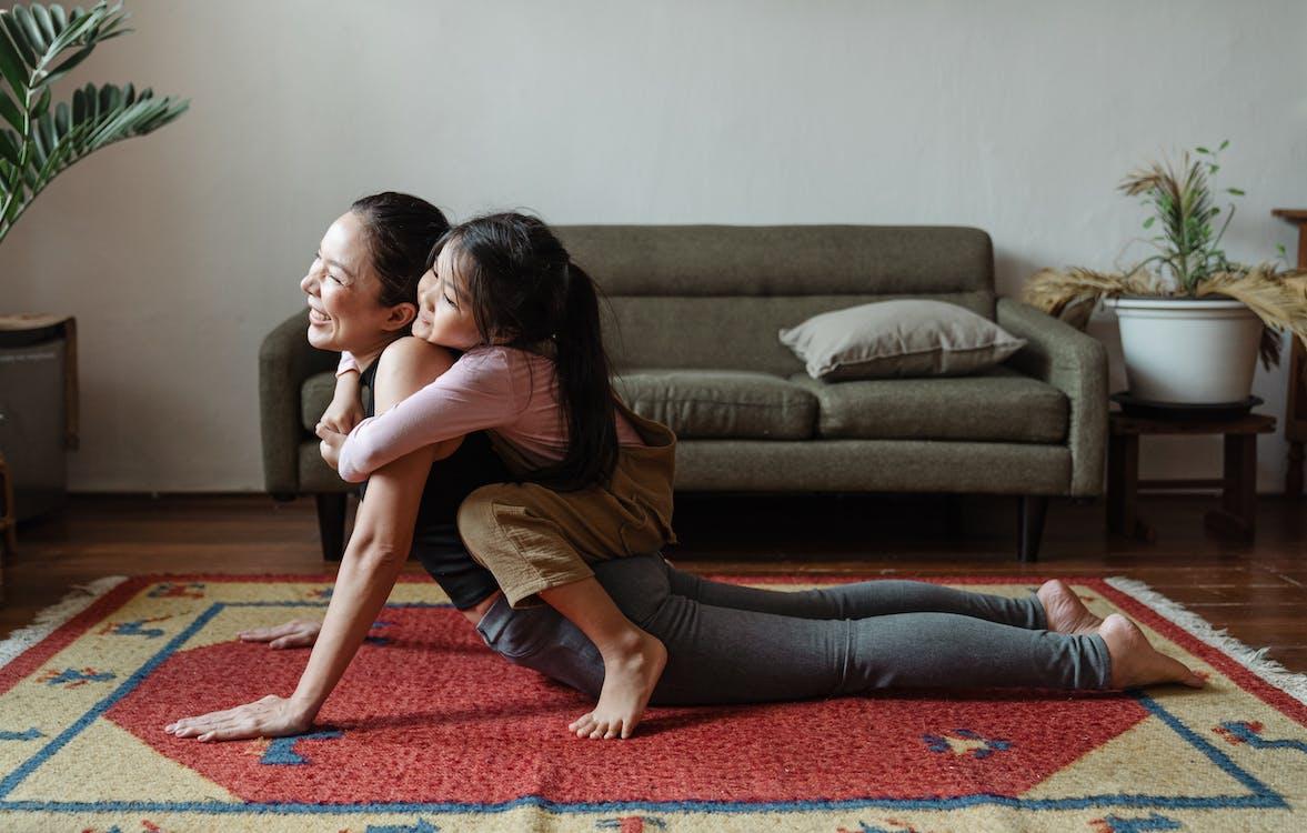 Photo of Girl Hugging Her Mom While Doing Yoga Pose