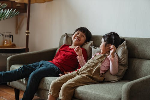 Photo of Two Kids Smiling While Sitting on Gray Sofa