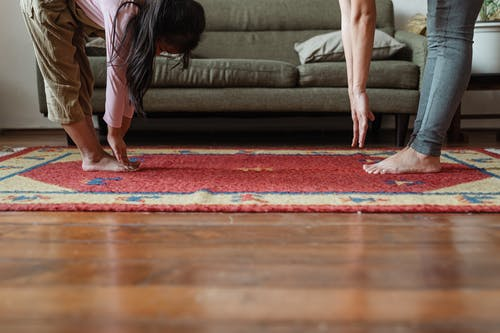 Side view of young ethnic woman stretching body with adorable girl while standing against each other on floor carpet near cozy sofa in modern living room in morning