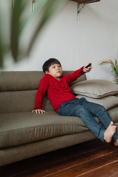 Content ethnic boy resting at home watching TV