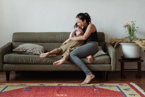 Photo of Woman Sitting on Couch While Hugging Her Child
