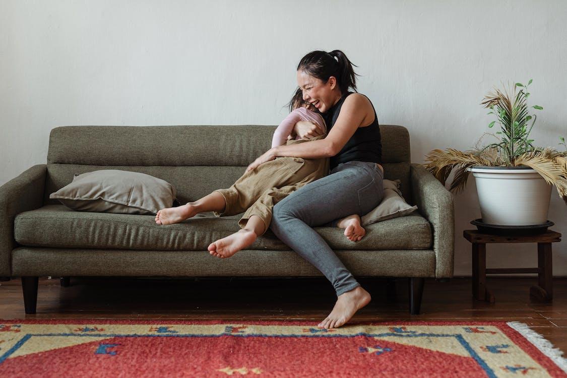 Foto Van Vrouw Zittend Op De Bank Terwijl Haar Kind Knuffelen