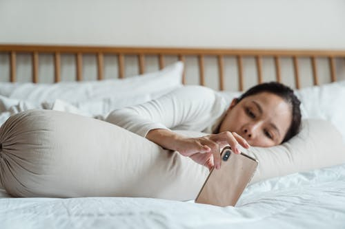 Lazy Asian woman using smartphone in bed