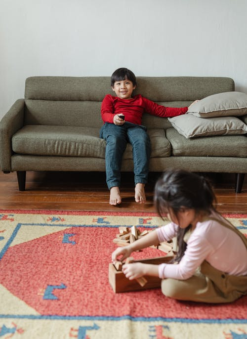 Smiling barefoot ethnic boy sitting on cozy sofa and switching TV channels with remote control while adorable sister playing jenga wooden block game sitting on floor carpet