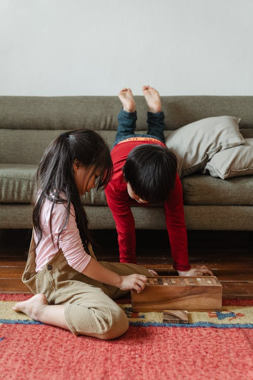 Adorable barefoot ethnic brother and sister playing tower game at home