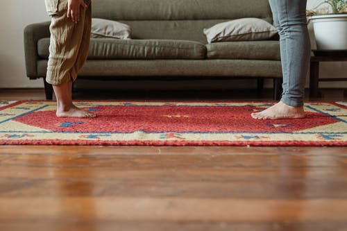 Photo of Two Persons Standing on Carpet