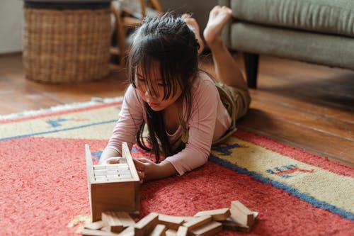Girl in White Long Sleeve Shirt Playing With Brown Wooden Blocks