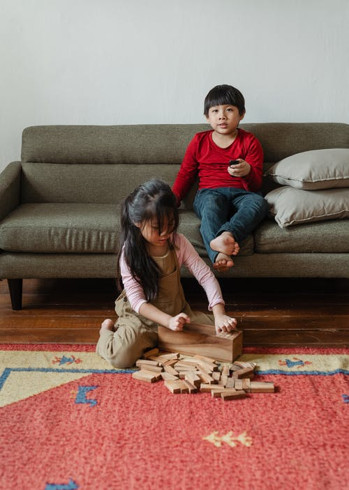 Barefoot ethnic boy sitting on cozy sofa and switching TV channels with remote control while cute sister playing wooden tower game sitting near on floor carpet at home