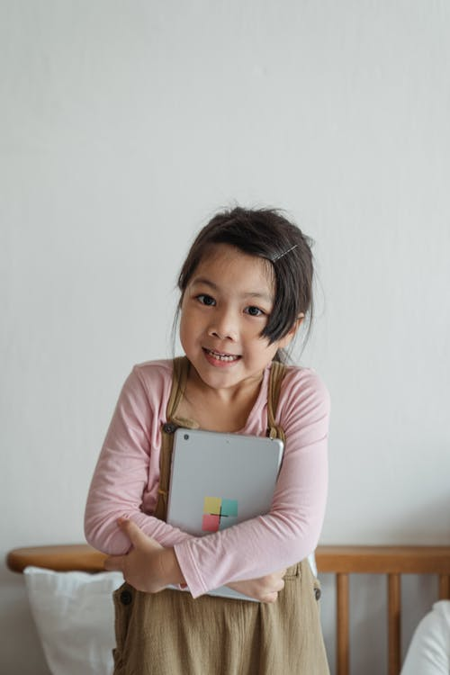 Smiling Asian girl cuddling tablet to chest