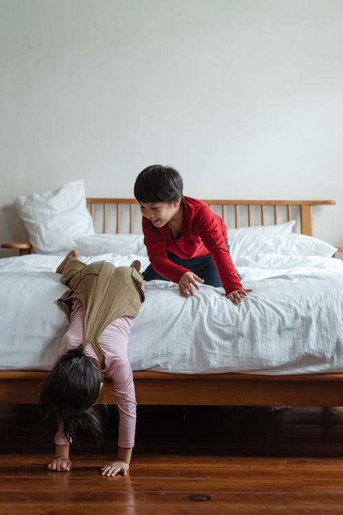 Full body smiling Asian kid in casual clothes looking at female friend sinking facedown from bed while children having fun together