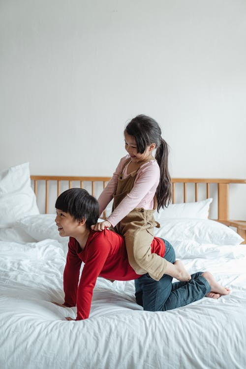 Positive ethnic brother giving piggyback ride to sister on bed