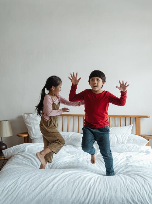 Joyful kids playing and jumping on bed