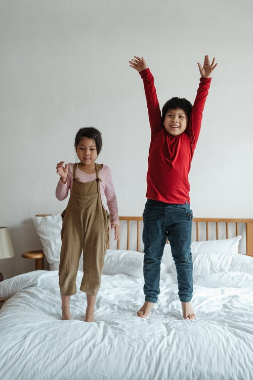Excited kids jumping on bed together