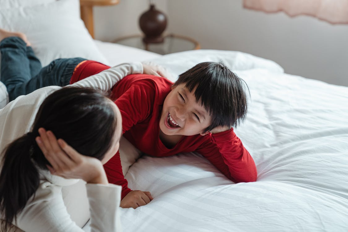 Photo of Mother and Son Lying Down on Bed