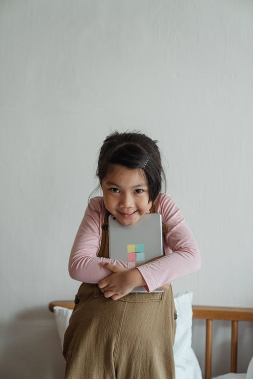 Photo of Girl Smiling While Holding Silver Tablet Computer