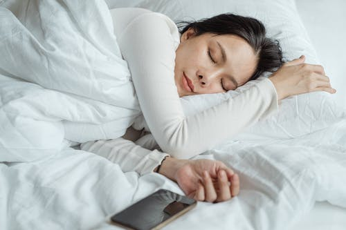 Calm Asian female wearing white pajama sleeping in comfortable bed with white sheets near modern mobile phone in morning