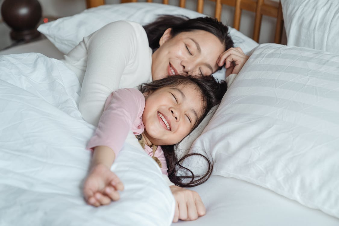 Cheerful mother and daughter resting in bed