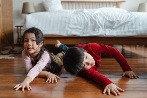 Happy little siblings playing on floor near bed