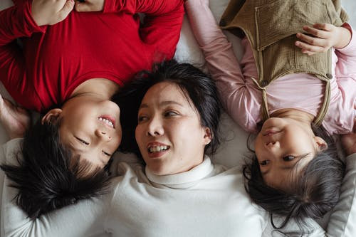 Photo of Woman and Her Children Lying on Bed
