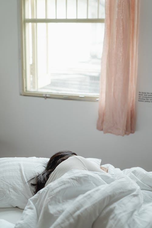 Woman Lying on Bed Near Window