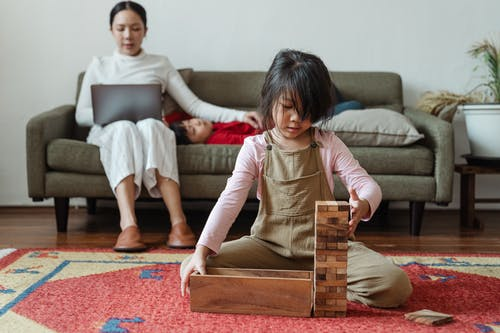 Photo of Girl Sitting on Floor While Playing With Jenga
