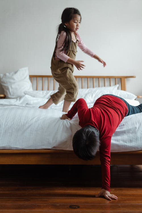 Cheerful adorable Asian brother and sister in casual clothing playing together on cozy bed with wooden bedhead in daylight