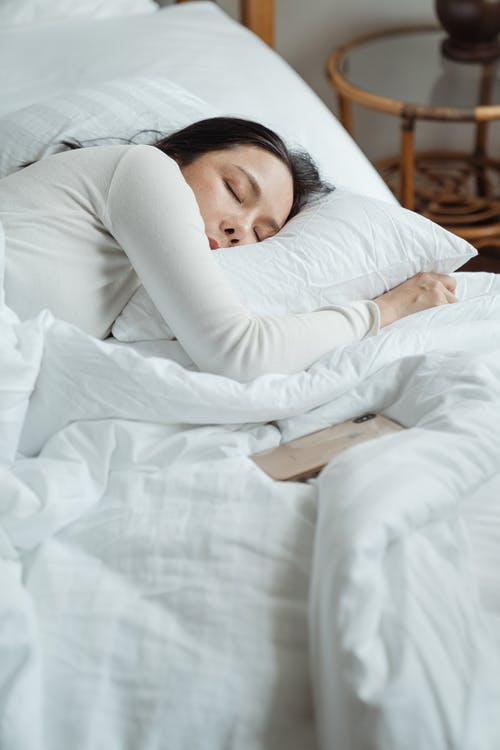 Woman in White Long Sleeved Shirt Lying on Bed