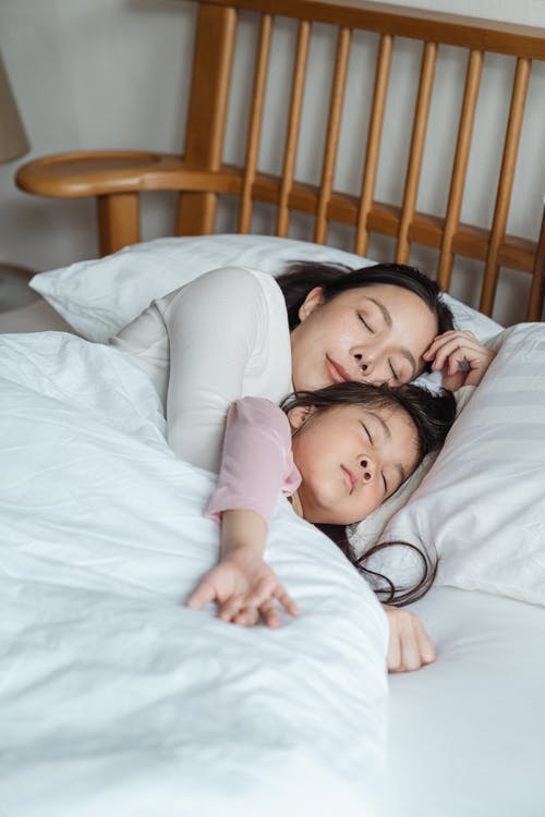Photo of Woman and Girl Lying on Bed