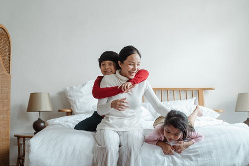 Cheerful mother with kids playing on bed