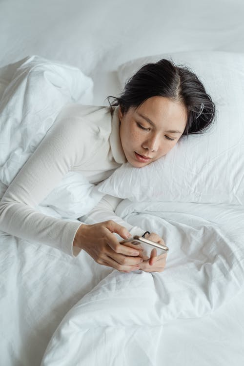 From above calm young Asian female in sleepwear waking up in morning and browsing mobile phone in cozy bed